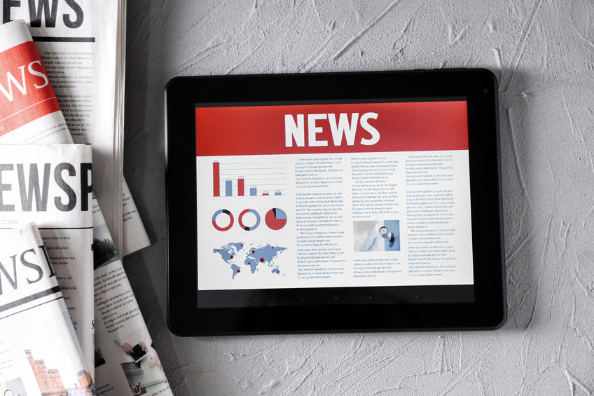 Tablet computer with news on screen on textured background